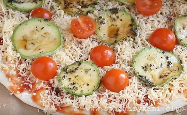 Затем в хаотичном порядке раскидываем на тесто половинки помидоров.