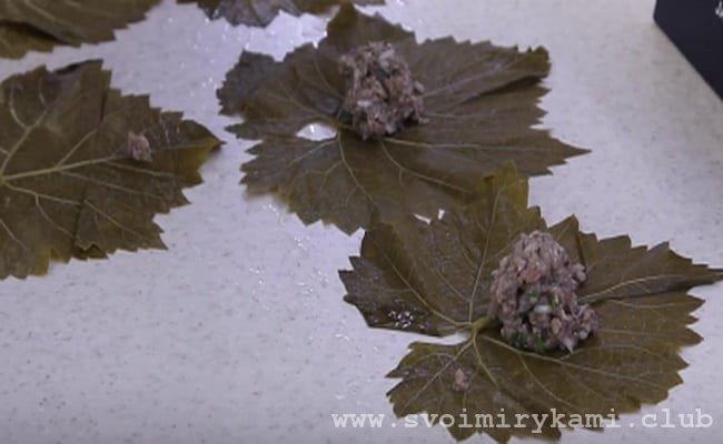 Выкладываем на виноградные листья 1/2 начинки.