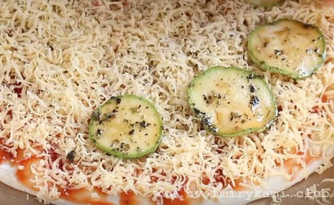 Раскладываем на тесто подготовленные маринованые кабачки.