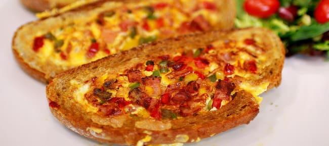 Готовая яичница с колбасой и сыром обжаренная в хлебе на сковороде.