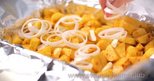 На картофель выкладываем кольца лука и чеснок