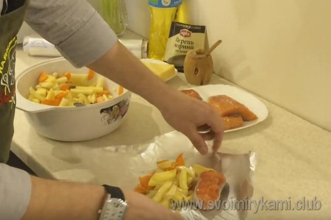 Порционно на кусок фольги выкладываем овощи и кусок рыбы.