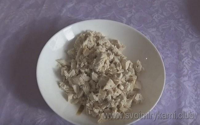 Режем кусочками отварное куриное филе.