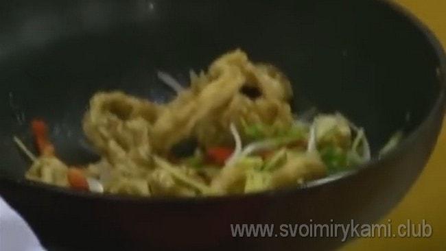 Возвращаем кальмары на сковороду и добавляем к ним нарезанные овощи и зелень.