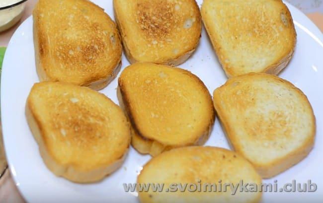 Чтобы пригоовить бутерброды со шпротами на праздничный стол, ломтики батона сначала поджариваем на сухой сковороде до румяности.
