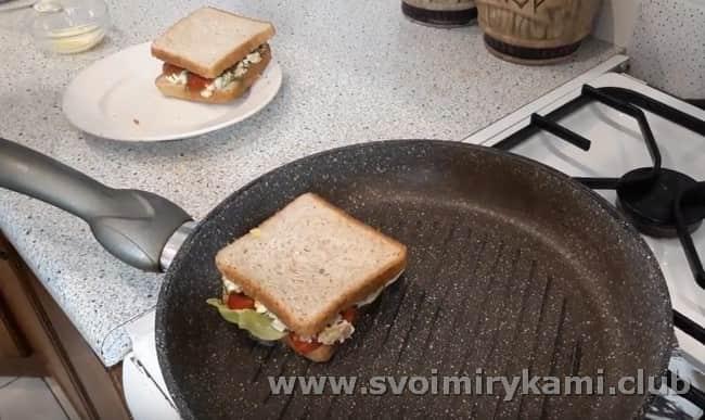 Обжариваем сэндвичи на сковороде гриль, смазав их сливочным маслом.