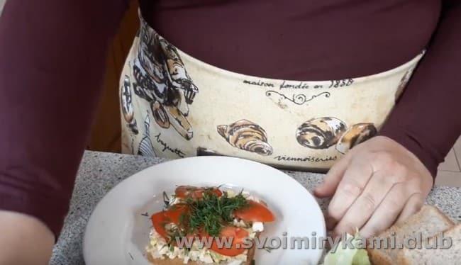 Ломтик хлеба смазываем начинкой, поверх которой выкладываем кусочки помидора, а также зелень.