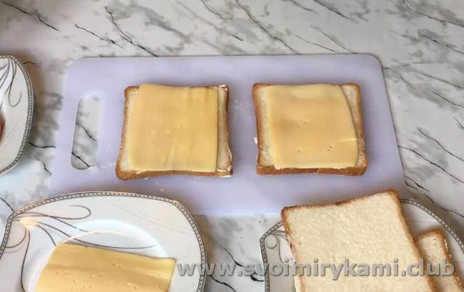 Смазав каждый ломтик хлеба маслом, кладем на них по слайсу сыра.