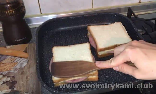 Кладем сэндвичи на сковородку и жарим, слегка прижимая.