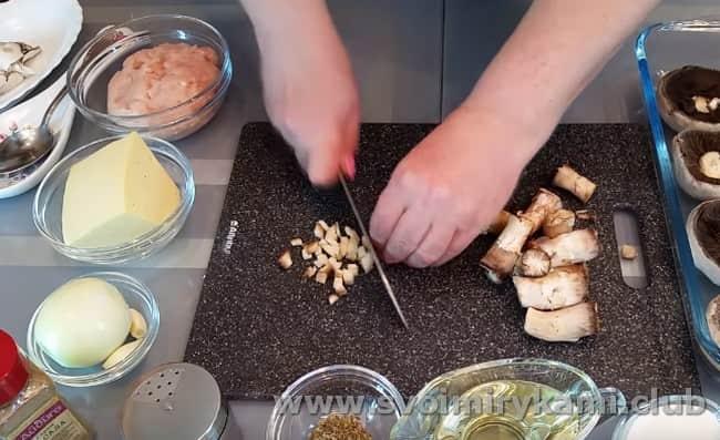 Шапочки грибов складываем в форму для запекания, а ножки мелко нарезаем.