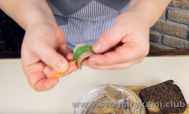 кусочек сельди вместе с зеленым перышком лука нанизываем на шпажку в форме паруса.