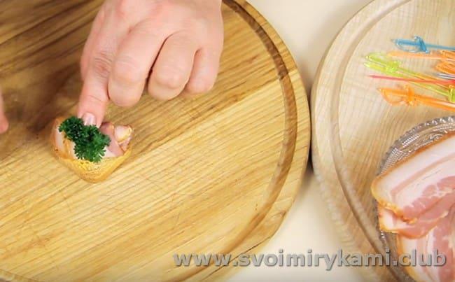на смазанный горчицей кусочек гренки выкладываем рулетик бекона и украшаем петрушкой.