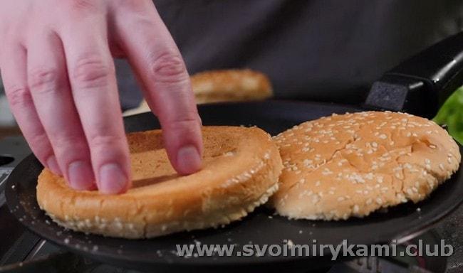 Перед тем как приготовить гамбургер в домашних условиях, разрезанную пополам булочку слегка подсушиваем на сухой сковороде.