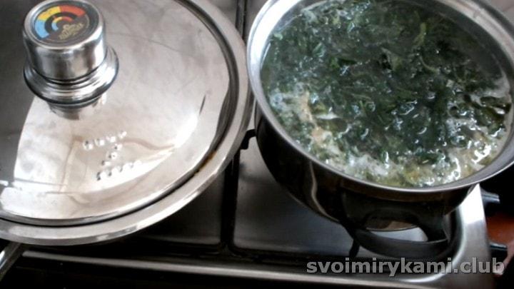 Выкладываем крапиву в кастрюлю к картофелю.