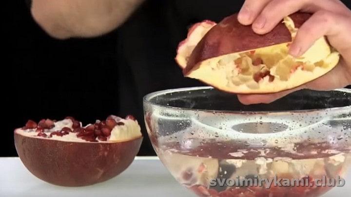Ложкой выбиваем зерна из одной половинки граната в миску с водой.