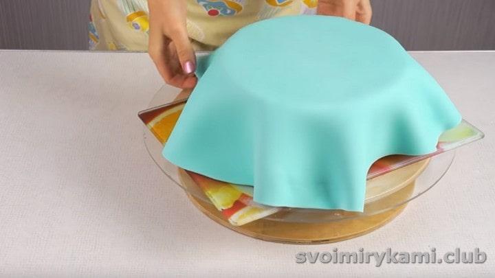Голубую мастику раскатываем, выкладываем на торт.