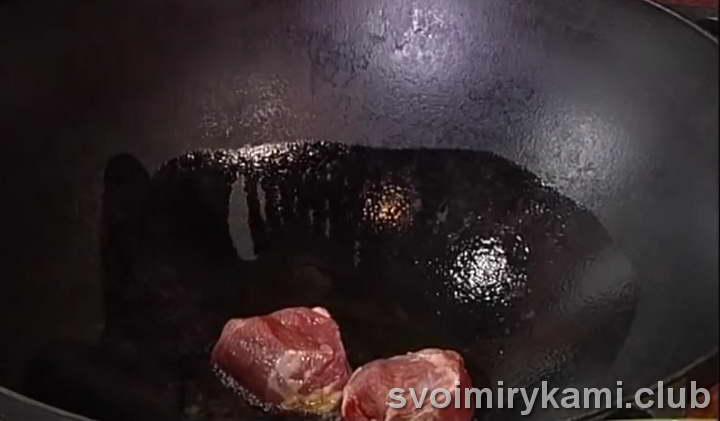 К разогретому маслу отправляем два крупных кусочка мяса