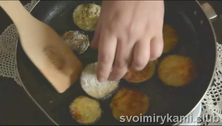 На разогретую сковородку выкладываем обваленные в муке кружки баклажанов